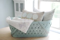 I bought this vintage baby bassinet--painted aqua--for throws and pillows in the living room or as a planter on the porch (after lining it, of course). Or could use it in the foyer? Any other ideas? It's a very large, sturdy wooden basket.