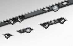 Ceiling recessed spotlighting system consisting of a structural module with frame made from aluminium and steel, to be installed as single luminaires (STAND-ALONE) or in continuous line (LINEAR), and interchangeable optic units with integral spotlights using high-performing Led, metal-halide and 12V halogen lamps.