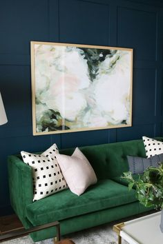 Living space with dark blue walls and a green velvet sofa