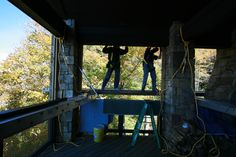 The guys of Carolina Window Fashions installing the motorized screen shades (60 ft off the ground)!