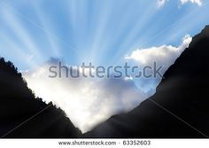 sun bursts through clouds from a dark mountain valley symbol for hope,call not to give up,light at the end of the tunnel - stock photo