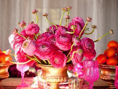 Statement with bold monochromatic arrangements. Artfully arrange dozens of bright pink ranunculus in a single gold vase to create a striking focal point
