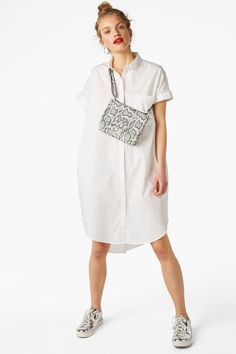 Large and in charge, this oversize sleeveless shirt dress is an awesomely dramatic interpretation of a closet staple. Hidden buttons and a perky pointed collar enhance the look even further.
