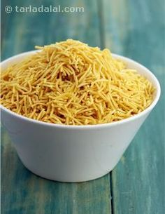 This crisp vermicelli made of gram flour is used to top almost all chaats. Mounds of different types of sevs are displayed at almost all farsan shops. The variety of flavours you get includes palak sev, garlic sev, pepper sev etc. Just name it and it is available! But did you know that making sev at home was as simple as this!