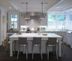 Rehkamp Larson Architects  Gorgeous white & silver kitchen design with white kitchen cabinets, white kitchen island, calcutta gold marble counter tops, glossy white subway tiles backsplash, industrial stools and tray ceiling.