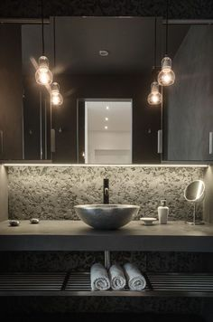concrete and metal bathroom vanity with a stone sink and an open shelf