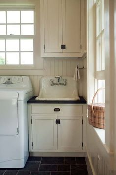 One end of this mudroom has a convenient laundry with an old sink built into the ivory-painted cabinets. Photo: Eric Roth