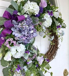 This beautiful wreath design is simple but stunning nonetheless. It boasts a wonderful mixture of garden foliages, including ivy, garden ferns, hanging vines and fuzzy gray Lambs ears. A beautiful lavender hydrangea is surrounded by snowball viburnum, lisianthus, clover, French #gardenvinesbeautiful