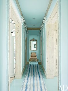 A hallway, painted in a Benjamin Moore blue, is lined with plaster palm trees | archdigest.com