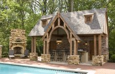 Love this pool house with outdoor kitchen, fireplace, and patio right by the inground pool.