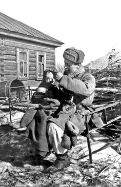 A Soviet Army soldier feeds a Russian baby he has found abandoned in an empty cabin in the village of Izvekov 14 March 1943