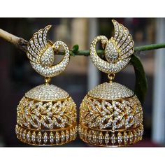 Stunning diamond like one gram gold plated jhumki studded with shinny white stones and emeralds.