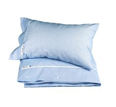 Pale blue bed linen with classic white piping, Newport logo labeling and white buttons. By Newport Collection