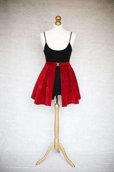 A SKIRTTAIL is a unique, handmade decorative over-skirt that can be worn over the top of any dress or any skirt/top combination that you already have on.   It is worn high on the waist and fastened neatly with a gold clasp. The gap in the centre of the fabric elegantly reveals the garment that you have on underneath, instantly updating your outfit.  Ruby Red Short Length available on Etsy.