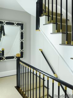 Custom brass and black railings in the stairwell make traditional newel posts glamorous.