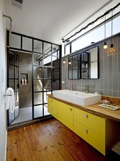bathroom aged wood floor, yellow cabinets, gray tile walls and glass pane shower