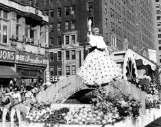 Film star Ginger Rogers brings Hollywood glamour to the streets of New York as she sits perched atop a flower float at the Macy's Thanksgiving Day parade in 1958.