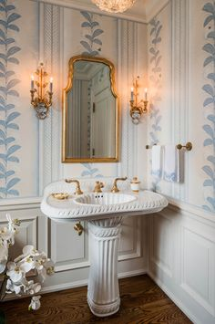 A lavish pedestal sink and fixtures blend nicely with the delicate wallpaper, creating a dressy powder room.