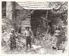 Sis, Coon, Pen (dog), & Aunt Mary Foust in Foust Hollow, Anderson Co., Tennessee. Mary Foust was the daughter of Daniel Foust.  She never left East Tennessee & lived to be around 100 years old.  When Teddy Roosevelt was visiting Tennessee she was considered the oldest living American at the time & he traveled to meet her & eat one of her home cooked meals.  Sis & Coon were her children &  her dog was named Pen.  An American chestnut tree can be seen in the upper right hand corner of the phot...