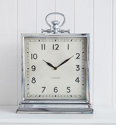 A large square polished silver colour mantel clock