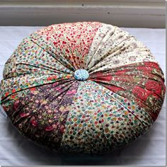 I bet I could make one of these by sewing a few fat squares into a strip and gathering the strip at the edges.