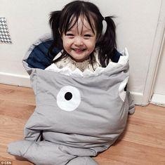Jae-eun flashes a mischievous grin as she is bundled inside a shark-themed sleeping bag...
