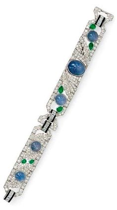 AN ART DECO STAR SAPPHIRE, EMERALD AND DIAMOND BRACELET, CIRCA 1925. Designed as an old European and single-cut diamond openwork band of foliate design, bezel-set with circular and oval cabochon star sapphires, enhanced by pear-shaped emeralds and baguette-cut diamonds, joined by baguette-cut diamond and buff-top onyx links, mounted in platinum. #ArtDeco