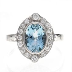 An aquamrine and diamond cluster ring, an oval cut aquamarine of surrounded by round brilliant cut diamonds with a rubover set diamond at north and south points, mounted in an white gold setting Jewelry Rings, Jewellery, Gemstone Engagement Rings, Diamond Cluster Ring, Aquamarine Blue, Gemstone Colors, Birthstones, Dubai, March