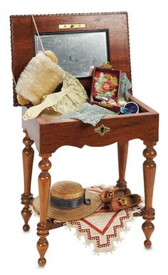 "Theriault's Antique Doll Auctions - French Wooden Necessaire Table with Accessories - 8"" (20 cm.) A wooden table with cherry finish, hinges open to reveal a storage compartment that contains an assortment of fashion accessories and sewing sundries,including folding fan,muff,blue silk knit fingerless gloves,silver mesh purse,brushes,combs,scissors,thimble,heeled tan leather shoes,straw bonnet and needlework. Excellent condition. French,circa 1890."