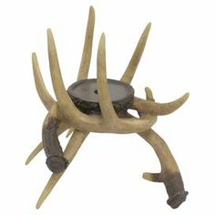 """Add a lodge-inspired touch to your decor with this rustic candleholder, showcasing an antler silhouette.  Product: CandleholderConstruction Material: ResinColor: NaturalAccommodates: (1) Candle - not includedDimensions: 10.25"""" H x 11"""" W x 12.6"""" D"""