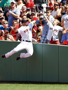 Pictures of the Year - Shane Victorino of the Red Sox leaps over the right field wall in an attempt for a foul ball in an Aug. 4 game against the Diamondbacks in Boston.