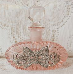 This is a very old pink Czech jewelry embellished perfume bottle with old pieces of rhinestone jewelry.