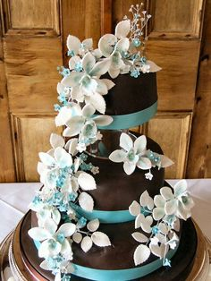 Chocolate brown wedding cake decorated with turquoise ribbons and white fondant flowers