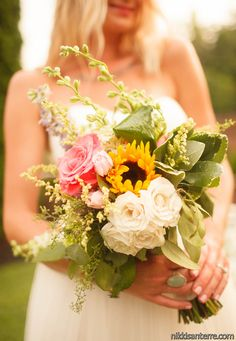 Whimsical Bridal Bouquet in assorted wildflowers like Roses, Sunflowers, Spray Roses, Larkspur, etc.