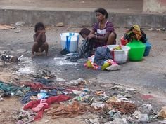A woman and her children washing clothes in the slums of India