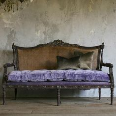 Bergére sofa with bluebell velvet squab cushion and smokey bronze scatter cushions.