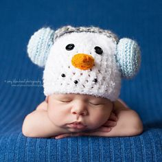 Baby Boy Frosty with Earmuffs Hat  Your baby boy will definitely stay warm in this hat! This adorable Baby Boy Frosty with Earmuffs Hat from Melondipity is an adorable snowman who is wearing earmuffs! This hat is a very high quality premier hand crafted hat made right here in the USA. The hat is a snow white with baby blue three dimensional ear muffs and a grey ear muff band. $30.99 USD