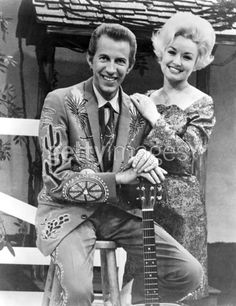 Dolly Parton & Porter Wagoner, 1967  Country singer Dolly Parton with her collaborator Porter Wagoner on the set of his TV show in circa 1967. Mr. Wagoner is wearing a Nudie Suit designed by Nudie Cohn of Nudie's Rodeo Tailors.
