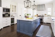 White and blue kitchen features white cabinets painted Benjamin Moore White Dove paired with calacatta gold extra marble countertops and a white subway tiles backsplash.