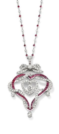 A ruby diamond heart pendant necklace  Designed as a calibre-cut ruby openwork heart entwined by a line of brilliant-cut diamonds suspending a central similarly cut diamond heart, to a diamond bow surmount, millegrain-set diamond drop highlights, and suspended on a spectacle-set ruby and diamond chain, length 41 cm, pendant length 6.2 cm. Edwardian or Edwardian style.