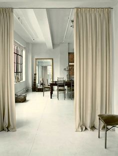 the NYC loft of Amsale Aberras - interior design by Vicente Wolf. I love how the curtain is used to create a separation and variation of texture in this really cool loft!