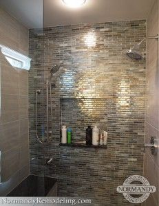 Love the glass tile in this shower!  It's absolutely stunning.  And the shower niche and bench complete the look.