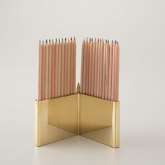 This eye-catching, V-shaped polished brass pencil holder is a great way to store up to 25 pencils or other writing utensils. Comes with 25 perfectly-sharpened colored pencils.
