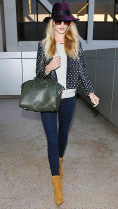 Rosie Huntington-Whiteley is travel-chic in a cool color palette - plum fedora, olive bag, dark jeans, and tan booties.