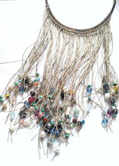 Collar con gargantilla de plata y multitiras de lino en macramé con adornos de cristal, perla, madera y metal.
