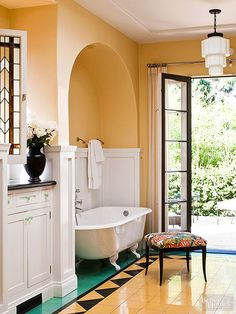 An arched alcove supplies an almost-private tub location, strategically set outside the bathroom's main traffic paths. The paneled wainscot and green-tile flooring further define the bathing chamber. Though the tub is set back, bathers are still able to enjoy verdant vistas through French doors that open to a patio and lush plantings./