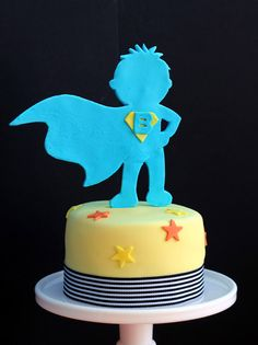 With this pic as insiration i thought of doing the following: Find a SuperHero figure in the web, print it in cardboard paper (so it can be thick) and place it on top of the kid's cake!