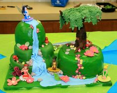 Pixie Hollow Birthday Cake - my first attempt at fondant.  Vanilla butter cake with strawberry Italian meringue buttercream covered with marshmallow fondant.  The tree was formed around a wire coat hanger/saran wrap base.  The waterfall is fondant, the fairies are store-bought, and the rest of the decorations are candy clay.