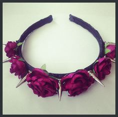 This is a headband featuring seven long liberty spikes and six maroon roses.