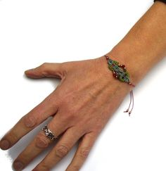 Ein geknüpftes **Armband** mit eingearbeiteten Rocailles, Glasschliffperlchen und Hämatith-Cubes.  Material: S-Lon Cord    Es ist mit Schiebeverschluss größenverstellbar und lässt sich somit...